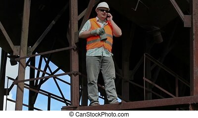 Worker witt cell phone and adjustable wrench in factory