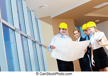 Indoor - Portrait of team of workers holding a project and...