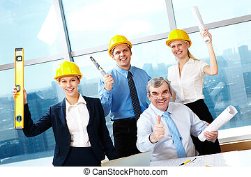 Happy workers - Portrait of four happy workers holding...