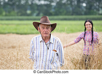 People at harvest - Senior man and young woman standing in...