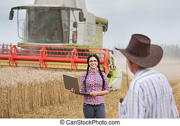 People at harvest - Young farmer woman with laptop standing...