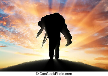 Soldier carries a wounded soldier at sunset - War and...