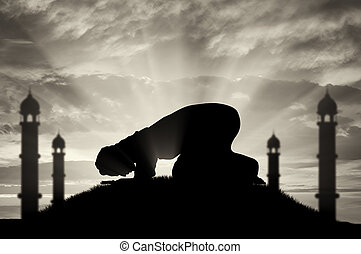 Muslim prays at sunset near the mosque - Religion Islam. A...