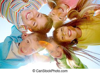 Joyful friends - Below view of happy children embracing each...