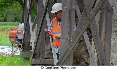 Construction worker using tablet PC and looking through...