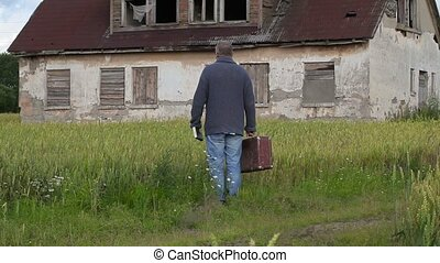Man with suitcase looking to old abandoned home and walking...