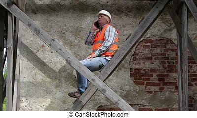 Construction worker sitting on wooden scaffolding and...