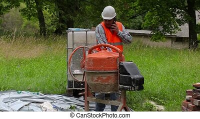 Construction worker talking on phone near concrete mixer