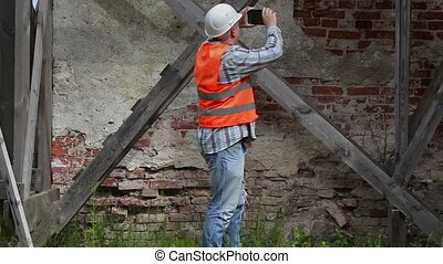 Construction worker take pictures on tablet PC near wooden...