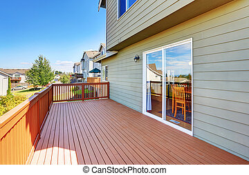 Empty wooden walkout deck with neighborhood view