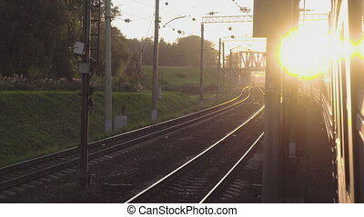 Suburban train at sunset - View from the window of the...