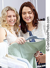 Girls shopping - Image of pretty girls chosing clothes in...