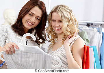 Two shoppers - Image of pretty friends chosing clothes and...