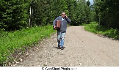 Man with suitcase talking on smart phone and walking