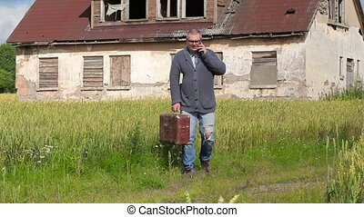 Man with suitcase talking on smart phone near abandoned...