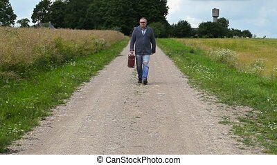 Man with suitcase on rural road