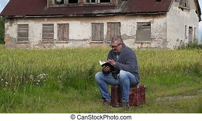 Man sitting on suitcase and reading book
