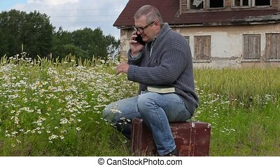 Man sitting on suitcase and talking on phone near chamomile...
