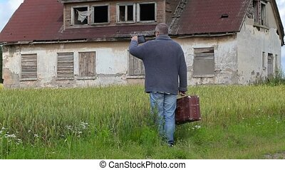 Man with suitcase take pictures on tablet PC near abandoned...