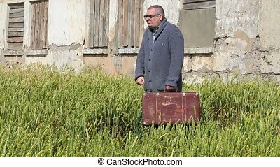 Man with suitcase walking near abandoned building
