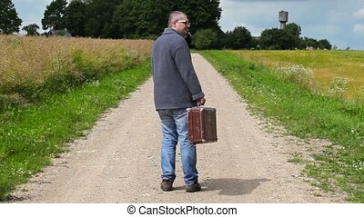 Man with suitcase walking away on rural road