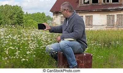 Man sitting on suitcase and take pictures on tablet PC near...