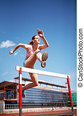 High jump - Image of young female jumping over barrier