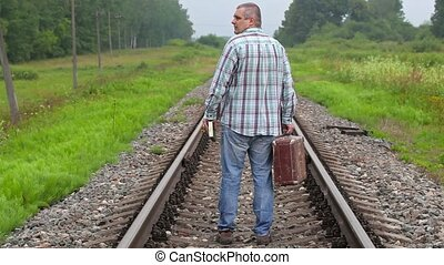 Man with book and suitcase walking away on railway