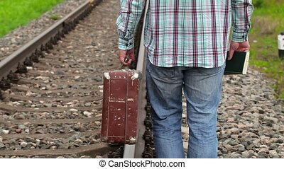 Man with book and suitcase on railway