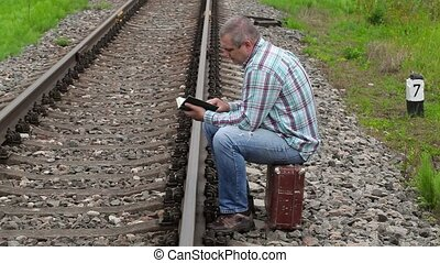 Man sitting on suitcase and reading book near railway