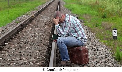 Man with book sitting on suitcase near railway
