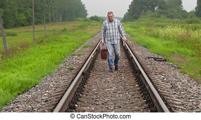 Man with book and suitcase walking on railway