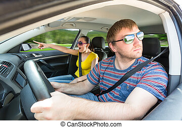 Couple driving in the car - Couple in the car, while man is...
