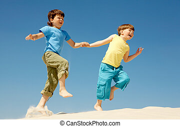 Runners - Photo of happy boys running down sandy beach and...