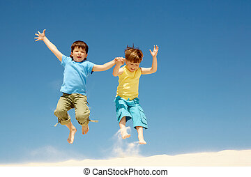 Fun - Photo of happy boys jumping on sandy beach and having...