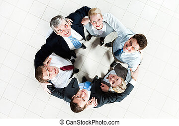 Unity - Above view of several business partners looking...