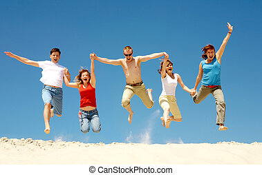 Dynamism - Photo of excited people jumping on sandy beach...