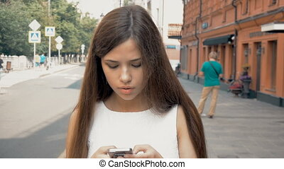 Beautiful girl walking on the city. Typing sms, I am using...