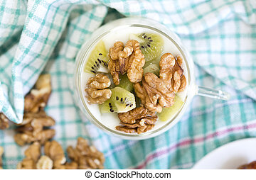 Glass with Plain yogurt with kiwi and nuts on a colored...