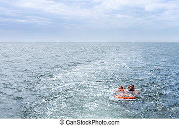 Man saves child in water - Man lifeguard with lifebuoy saves...