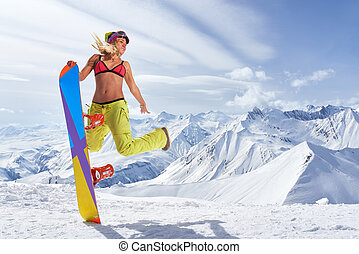 Happy young woman with snowboard jumping in winter sportswear