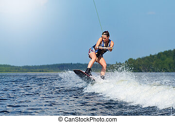 Slim brunette woman riding wakeboard on motorboat wave in...