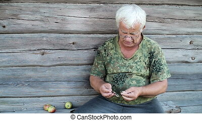 Senior man cleans a small dried fish. Wooden old house in...