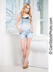 Young beautiful woman posing in short denim overalls near...