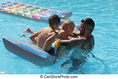 A father with his two young children in a swimming pool...