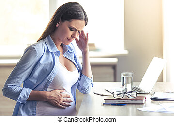 Beautiful pregnant business woman is having headache,...