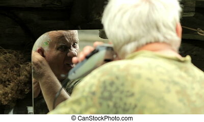 A middle aged man dressed in a khaki t-shirt, shaving his...