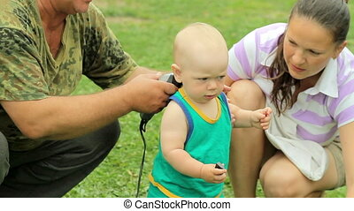 Mother and grandfather cutting baby hair by hair clipper in...