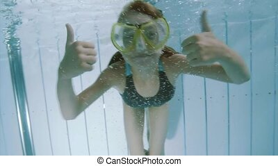 Underwater girl in aquapark - Child submerging under water...