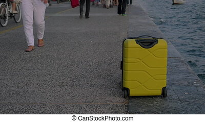 Suitcase on wheels stands on promenade In the background...